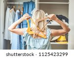 girl near a wardrobe with... | Shutterstock . vector #1125423299