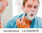 a handsome man shaves his beard ... | Shutterstock . vector #1125465878