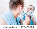 a handsome man shaves his beard ... | Shutterstock . vector #1125465884
