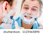 a handsome man shaves his beard ... | Shutterstock . vector #1125465890