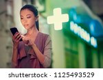 Small photo of A young asian woman is locating a pharmacy store at night with her smart phone mobile device. Communicate about open pharmacies at night, using navigation to locate stores, maps, health, on call