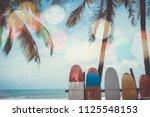 many surfboards beside coconut... | Shutterstock . vector #1125548153