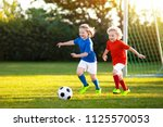 kids play football on outdoor... | Shutterstock . vector #1125570053