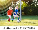 kids play football on outdoor... | Shutterstock . vector #1125599846