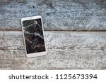 mobile phone with broken screen ... | Shutterstock . vector #1125673394
