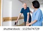 happy elder man with walker... | Shutterstock . vector #1125674729