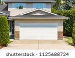wide garage door of residential ... | Shutterstock . vector #1125688724