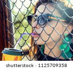 a girl drinks from a plastic... | Shutterstock . vector #1125709358