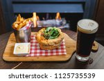 close up of meat pie and chips... | Shutterstock . vector #1125735539