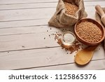 wheat in a plate wooden table... | Shutterstock . vector #1125865376