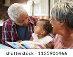 grandparents reading book with... | Shutterstock . vector #1125901466