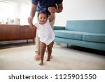 father encouraging baby... | Shutterstock . vector #1125901550