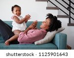 mother lying on sofa at home... | Shutterstock . vector #1125901643