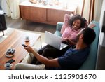 couple sitting on sofa at home... | Shutterstock . vector #1125901670