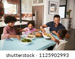 family enjoying meal around... | Shutterstock . vector #1125902993