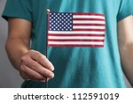 A man in a teal shirt hold a small American flag out in front of him.