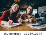 Stock photo positive carefree hipster girl writing essay with excited idea in textbook sitting near female 1125913379