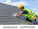 Roof repair, worker with white gloves replacing gray tiles or shingles on house with blue sky as background and copy space, Roofing - construction worker standing on a roof covering it with tiles. - stock photo