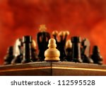 A little pawn is alone in the corner against everybody - stock photo
