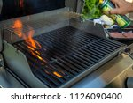spraying nonstick on grill... | Shutterstock . vector #1126090400