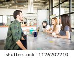Stock photo business man and women sitting in cafeteria having coffee and chatting 1126202210