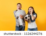 Small photo of Young win couple, woman man, football fans holding bundle of dollars, cash money, soccer ball, cheer up support team isolated on yellow background. Sport bet excitement ardor family lifestyle concept