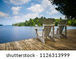 two muskoka chairs sitting on a ... | Shutterstock . vector #1126313999