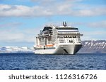 white cruise liner against the background of mountains and fjords in the North sea