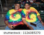 Small photo of WEST SACRAMENTO, CA/U.S.A. - JUNE 29, 2018: Vim Tillman and Sunny Jarvis wear matching tie-dye San Francisco Giants t-shirts with rainbow hats at the River Cats Equality Night baseball game.