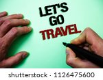 Small photo of Word writing text Let'S Go Travel. Business concept for Going away Travelling Asking someone to go outside Trip Green background grey shadow important thoughts temple message idea.