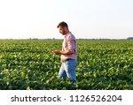 young farmer walking in filed... | Shutterstock . vector #1126526204