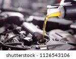 motor oil pouring to car engine. | Shutterstock . vector #1126543106
