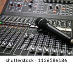 microphone rests on an audio... | Shutterstock . vector #1126586186