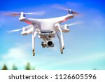 white quadrocopter is flying... | Shutterstock . vector #1126605596