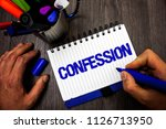 Small photo of Handwriting text writing Confession. Concept meaning Admission Revelation Disclosure Divulgence Utterance Assertion Man hold holding marker notebook ideas markers wooden table inspiration.