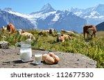Jug of milk and bread against herd of cows. Jungfrau region, Switzerland - stock photo
