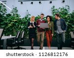 group of coworkers looking at a ... | Shutterstock . vector #1126812176
