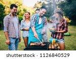 happy friends enjoying barbecue ... | Shutterstock . vector #1126840529