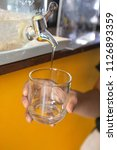 hand of woman filling glass at... | Shutterstock . vector #1126893359
