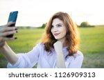 young blond girl doing selfie... | Shutterstock . vector #1126909313
