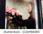 florist woman on the work on... | Shutterstock . vector #1126986083