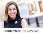 Portrait of a successful woman in the city looking happy - stock photo