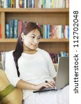 Portrait of beautiful asian woman using laptop in student lounge - stock photo
