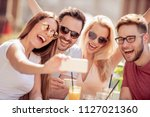 four laughing friends enjoying... | Shutterstock . vector #1127021360