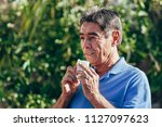 elderly man blowing his nose on ...   Shutterstock . vector #1127097623