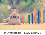 Small photo of Loan or lending cash to buy asset concept : Loan bag and color wood bar graphs in different height on a table, depicts a borrower always borrow money from lender in higher amount and never payback