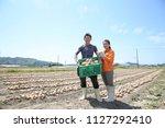 a young farmer couple... | Shutterstock . vector #1127292410