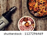 Small photo of Lunch on work place. Homemade mini cherry rolls in a baking form and two rolls on a plate and electric drill on vintage wooden background. Dissonant disharmonious composition. Lunch break. Toned