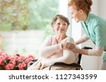 young nurse helping an elderly... | Shutterstock . vector #1127343599