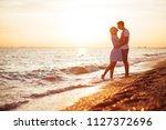 young happy couple on seashore... | Shutterstock . vector #1127372696